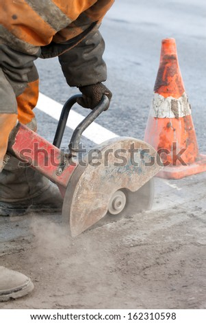 Cutting asphalt road for repair with angle grinder; road works; upgrading road surfaces; vertical orientation