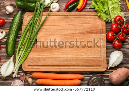 Cutting board and vegetables on wooden background