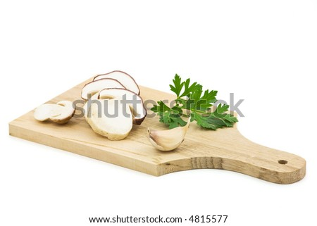 Cutting board, ceps, garlic and parsley.