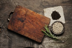 Cutting Board, rosemary and spices on a old wooden table
