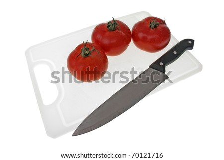 Cutting board with a knife and tomato isolated on a white background.