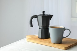 Cutting board with cup of fresh coffee and coffee maker on white table against light background, space for text