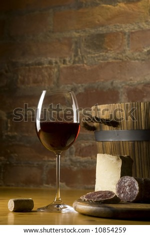 Cutting board with genuine Italian food in a rural kitchen. Red wine glass, ripe hard cheese from ewe\'s milk and sausage. Warm ray of light in the background. Space for text
