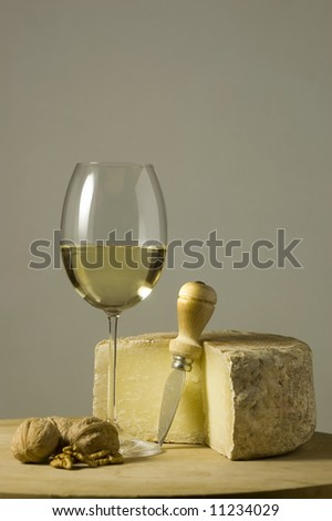 Cutting board with genuine Italian food. White wine glass, ripe hard cheese from ewe\'s milk and walnuts. Space for text