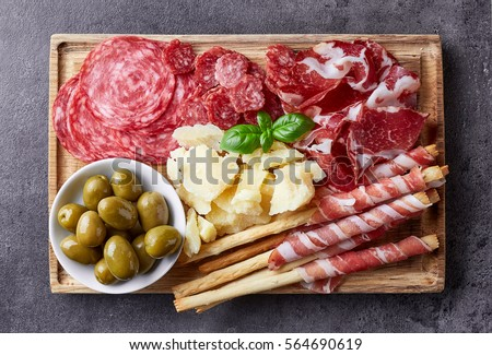 Shutterstock Cutting board with prosciutto, salami, cheese,bread sticks and olives on dark stone background. From top view