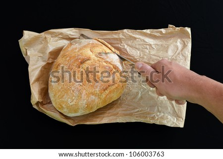 Cutting bread, Hand with knife and bread on paperbag isolated on black