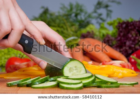 Cutting cucumber and vegetables on background
