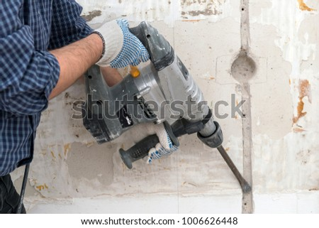 Cutting electrical chase in the concrete wall with hammer drill