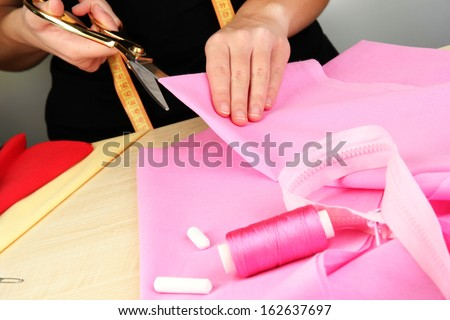 Cutting fabric with tailors scissors  #162637697