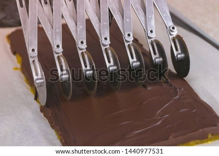 Cutting fillings for chocolate candies praline with apricot marmalade using wheel stainless steel cutter #1440977531