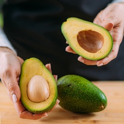Cutting fresh, organic avocado, superfood rich in monosaturated fat, vitamins, minerals, fibers and phytonutrients