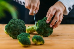 Cutting fresh organic broccoli, superfood rich in vitamin K, vitamin C, folic acid, potassium, phytonutrients and fibers