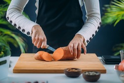 Cutting Fresh Organic Sweet Potato, superfood rich in tryptophan, potassium, vitamin C, phytonutrients and dietary fibers