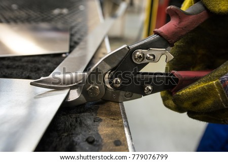Cutting of metal sheets with powerful industrial hand-operated scissors in the shop of the plant for the production of body elements of subway cars