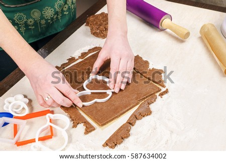 Cutting out dough for shaped as a rabbit gingerbread with the help of a plastic pattern. - Shutterstock ID 587634002