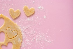 Cutting out heart-shaped cookies from flour-flavored dough on a light pink surface. Top view, the process of preparing homemade treats for Valentine's Day.