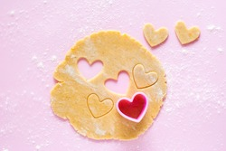Cutting out heart-shaped cookies from rolled dough with a pink plastic mold. Top view on flour sprinkled gently pink background.
