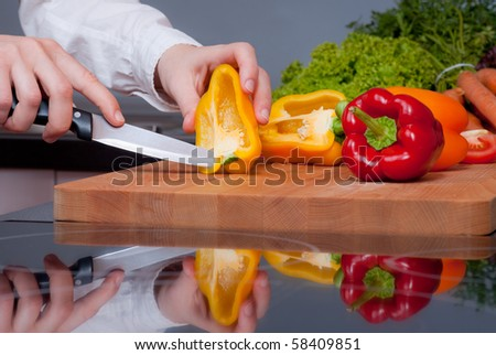 Cutting pepper on board with reflection on induction cooktop.