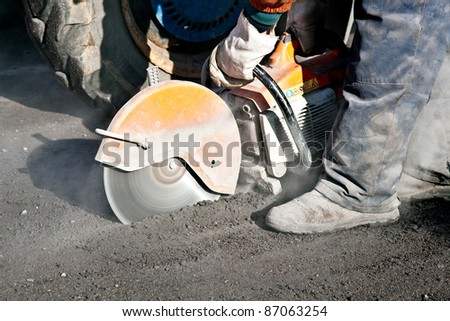 Cutting road works with cut off saw - stock photo