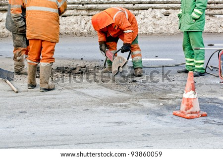Cutting road works with hydraulic driven angle grinder, upgrading road surfaces; horizontal orientation