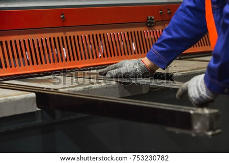 cutting sheet metal in large hydraulic guillotine shears. Work at the factory