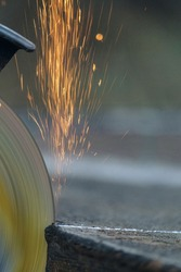 Cutting sheet steel structures an electric cut-off wheel grinding machine. Detail. Speedy rotation disc with sparks.