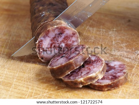 cutting spanish salami slices with a knife