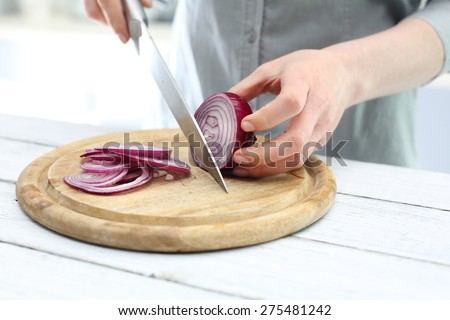 Cutting the onion into slices. Woman cut red onion