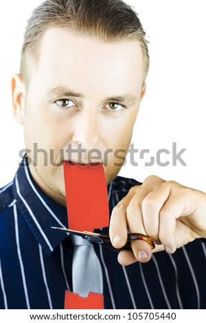 Cutting the red tape concept with a young man holding one end of the tape between his teeth while cutting it with a pair of scissors in his attempt to cut through bureacracy and officialdom