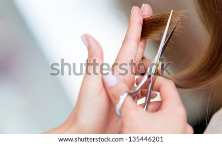 Cutting the split ends of damage hair at the beauty salon