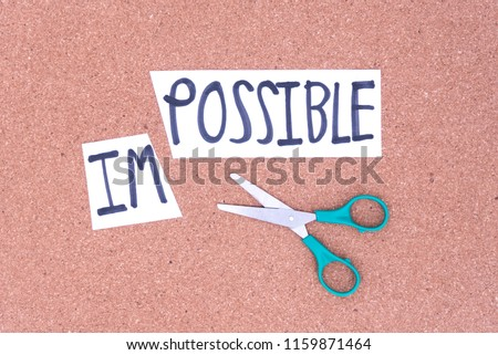 Cutting the word in paper note impossible to read possible, concept for self belief, positive attitude and motivation.