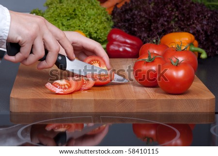 Cutting tomato on wooden board with reflection and vegetables on background.