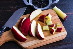 Cutting Up a Red Delicious Apple: Slicing a red apple into chunks on a wood cutting board