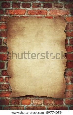 cutting vintage aged paper on the red brick wall
