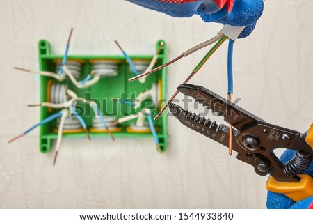 Cutting wires with wire cutter pliers. Installation of a square plastic electrical junction box for hidden wiring on the wall in the house. Repair, updating and maintenance of home electric networks.