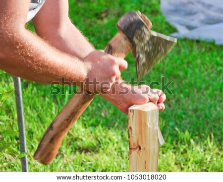 Cutting wood for kindling. Men's hands, axe and firewood. Dynamics of impact with an ax #1053018020