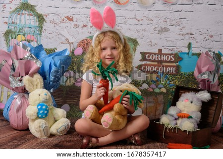 Cuty little girl in the ears of the Easter bunny holds a rabbit a sausage, with Easter background scenery. The child smiles Foto stock ©