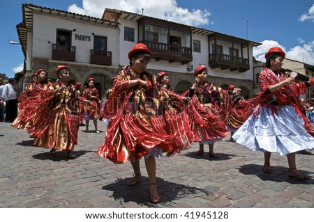 CUZCO, PERU - OCTOBER 8: Women in traditional red dresses and hats dance in the Virgen del Rosario Festival near the Plaza de Armas in Cuzco, Peru on October 8, 2009