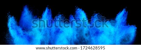 Photo of  cyan blue holi paint color powder explosion isolated on dark black background. industry beautiful party festival concept