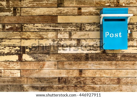 Cyan (Light blue) postbox on the old rough wooden wall #446927911