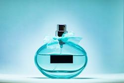 Cyan perfume glass bottle on light blue background. Eau de toilette. Eau de parfum. Beautiful composition of green blue perfume bottle.