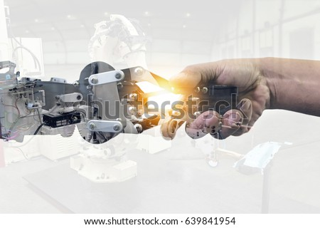 Cyber communication and robotic concepts. Industrial 4.0 Cyber Physical Systems concept. Double exposure of Robot and Engineer human holding hand with handshake and automate robot arm background.