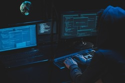 Cyber criminal hacking system at monitors, hacker attack web servers in dark room at computer with monitors sending virus using email vulneraility. Internet crime, hacking and malware concept.