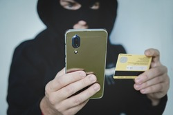 Cyber criminal in balaclava enters the information of a personal bank account. Credit card fraudulent scheme. Stealing cyber money using mobile. New ways of fraudulent transactions via online banking.