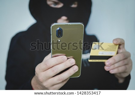 Cyber criminal in balaclava enters the information of a personal bank account. Credit card fraudulent scheme. Stealing cyber money using mobile. New ways of fraudulent transactions via online banking. Stock photo ©