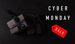 Cyber Monday sale shopping concept, Top view of gift box wrapped in black paper and black bow ribbon, studio shot on black background