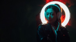 Cyber music. Night neon banner. Futuristic technology. Blue red light Asian girl with circle halo listening sound in headphones in color smoke on dark night copy space background.