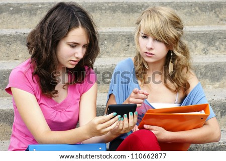 Cyber or online bullying concept with two young women students or teenager girls shocked at the text they are reading on their cell phone, perfect for awareness.
