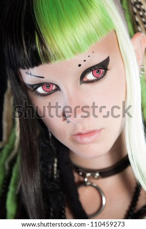 Cyber punk girl with green blond hair and red eyes isolated on black background. Expressive face. Studio shot.
