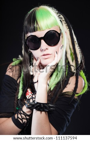 Cyber punk girl with green blond hair and red eyes isolated on black background. Wearing black sunglasses. Expressive face. Studio shot.